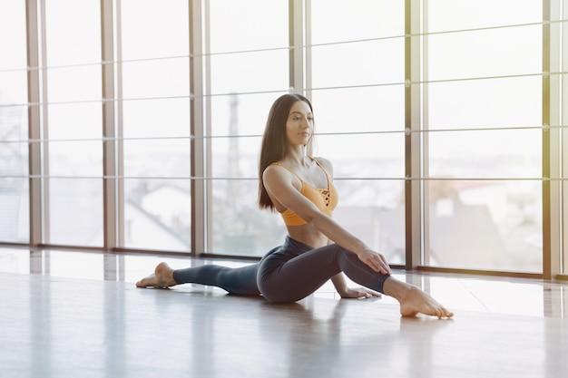 Jeune jolie fille faisant du fitness avec yoga sur le sol