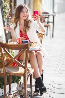 Jeune jolie fille faisant selfie sur téléphone portable. belle femme bouchent le portrait à l'extérieur. jolie dame tenant mobile.