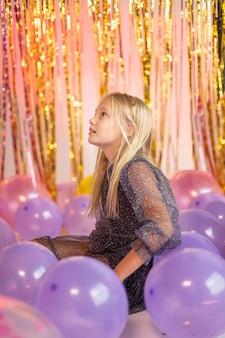 Jeune jolie fille à la fête avec des ballons