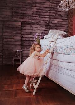 Jeune jolie fille grimpant sur un tas de matelas