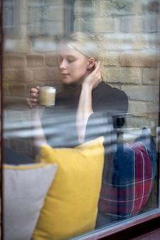 Jeune jolie fille implantation près de la fenêtre et boire du café ou du thé dans le café. pause café.