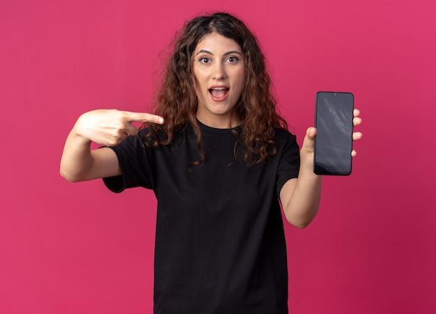 Jeune jolie fille impressionnée montrant un téléphone portable à un appareil photo pointant vers elle