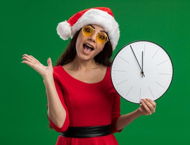 Jeune jolie fille impressionnée portant un bonnet de noel et des lunettes tenant une horloge montrant une main vide isolée sur un mur vert
