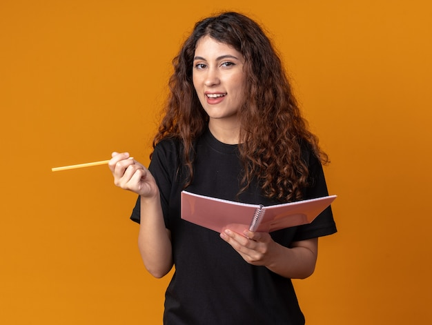 Jeune jolie fille impressionnée tenant un crayon et un bloc-notes