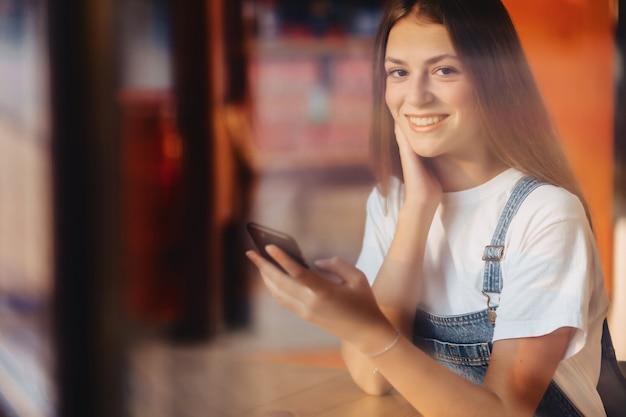 Jeune jolie fille jolie au café avec verre à vitre throuth et café