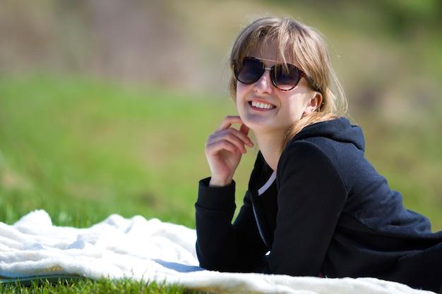 Jeune jolie fille jolie blonde en pull noir et lunettes de soleil foncées se trouve sur une serviette blanche sur l'herbe verte, profitant de la nature et d'une chaude journée ensoleillée souriant joyeusement à huis clos montrant de merveilleuses dents blanches.