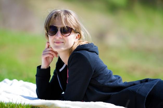 Jeune jolie fille jolie blonde en pull noir et lunettes de soleil foncées se trouve sur une serviette blanche sur l'herbe verte, profitant de la nature et d'une chaude journée ensoleillée souriant joyeusement à huis clos.