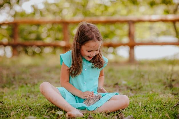 Jeune jolie fille jouant avec un petit hérisson