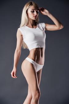 Jeune jolie fille en lingerie blanche sexy sur mur gris
