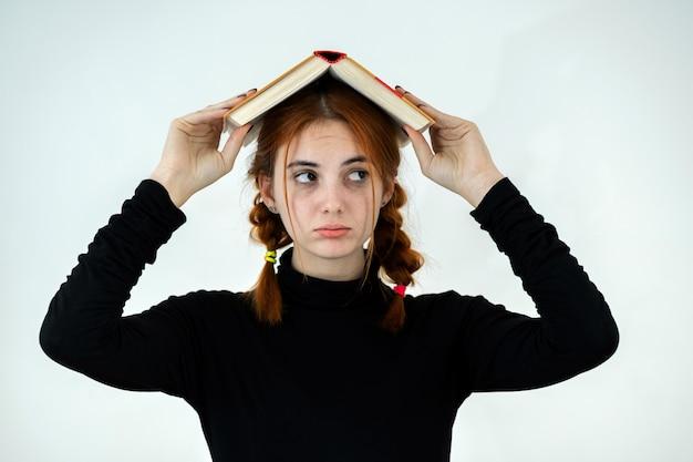 Jeune jolie fille avec un livre ouvert sur la tête. concept de lecture et d'éducation.