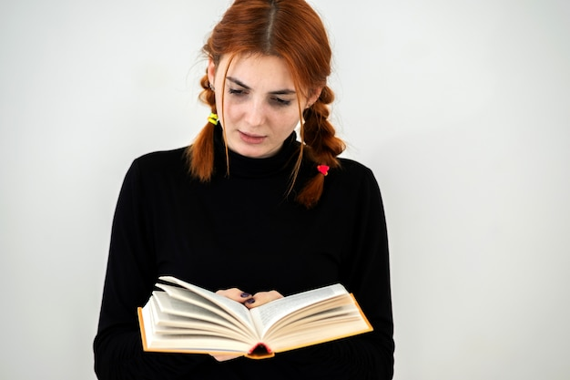 Jeune jolie fille a lu un livre ouvert dans ses mains. concept de lecture et d'éducation.