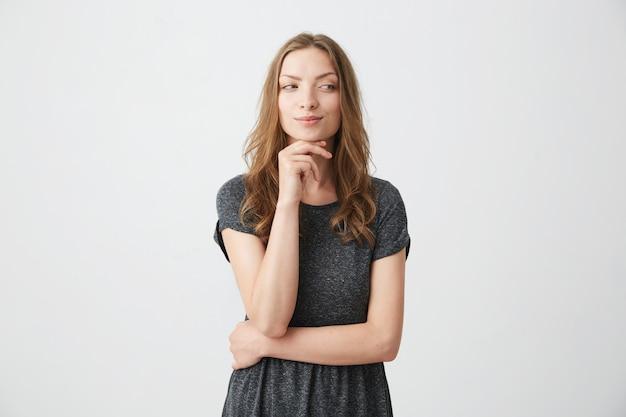 Jeune jolie fille ludique à la recherche de côté avec la main sur le menton.