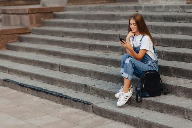Jeune jolie fille avec mallette assis dans les escaliers et écrit sms sur téléphone