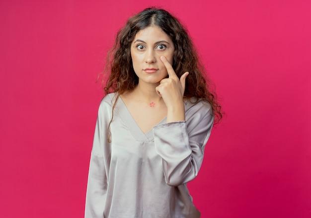 Jeune jolie fille mettant le doigt sur l'oeil isolé sur un mur rose