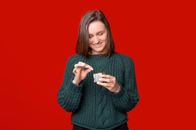 Jeune jolie fille ouvre un petit cadeau en argent sur fond rouge.