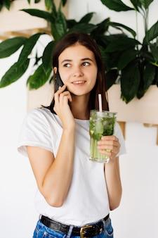 Jeune jolie fille parler téléphone mobile et boire un smoothie en se tenant debout à la table dans un café