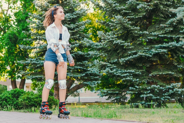 Jeune jolie fille patinage dans le parc