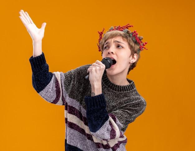 Jeune jolie fille portant une couronne de tête de noël tenant un microphone près de la bouche levant la main à la recherche de chant isolé sur fond orange