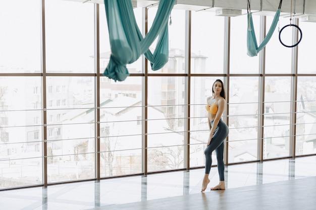 Jeune jolie fille posant au gymnase, silhouette douce, fitness et yoga