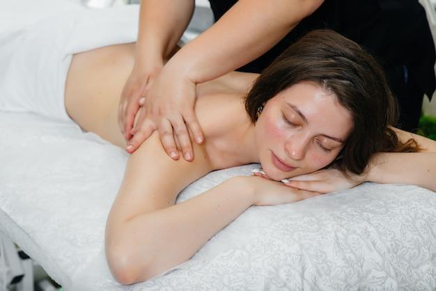 Une jeune jolie fille profite d'un massage cosmétologique professionnel au spa. soin du corps. salon de beauté.