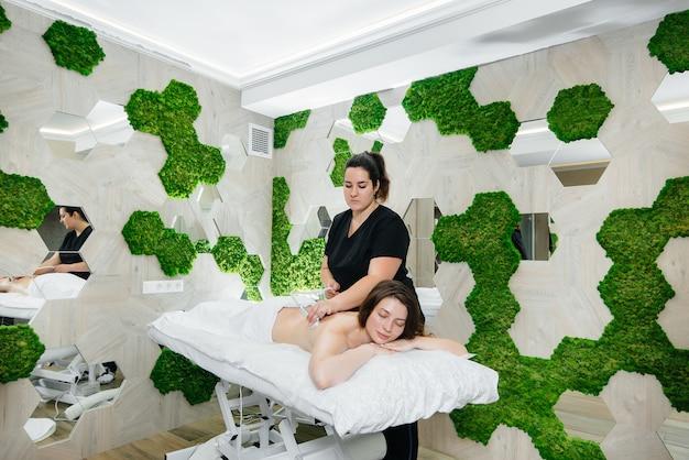 Une jeune jolie fille profite d'un massage professionnel sous vide au spa. soin du corps. salon de beauté.
