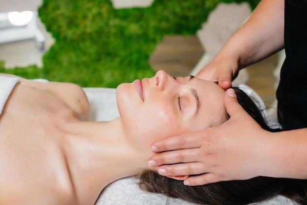 Une jeune jolie fille profite d'un massage professionnel de la tête au spa. soin du corps. salon de beauté.