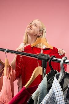 La jeune jolie fille regardant des robes et l'essayer en choisissant au magasin