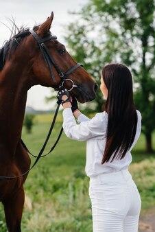 Une jeune jolie fille rider pose près d'un étalon pur-sang dans un ranch