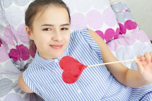 Jeune jolie fille rit, mange une sucette en forme de coeur