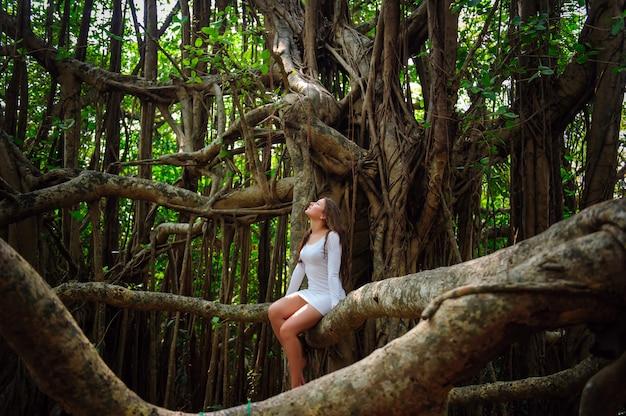 Jeune jolie fille en robe blanche courte sur banyan dans une chaude journée d'été