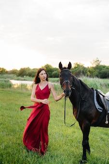 Une jeune jolie fille en robe rouge pose sur un ranch avec un étalon pur-sang au coucher du soleil. aimer et prendre soin des animaux.