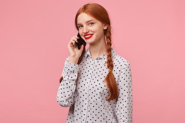 Jeune jolie fille rousse avec des tresses vêtue d'une chemise à pois blanche tenant un téléphone près de l'oreille avec la main parler à quelqu'un qui regarde avec le sourire, isolé