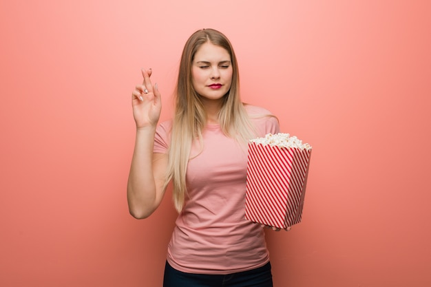 Jeune jolie fille russe croise les doigts pour avoir de la chance. elle tient des pop-corn.