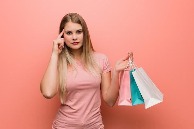 Jeune jolie fille russe pense à une idée. elle tient un sac à provisions.