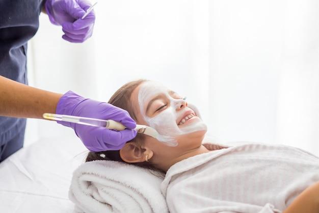 Jeune jolie fille s'amusant dans la chambre avec un masque facial à l'argile