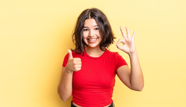 Jeune jolie fille se sentant heureuse, étonnée, satisfaite et surprise, montrant des gestes d'accord et le pouce levé, souriant