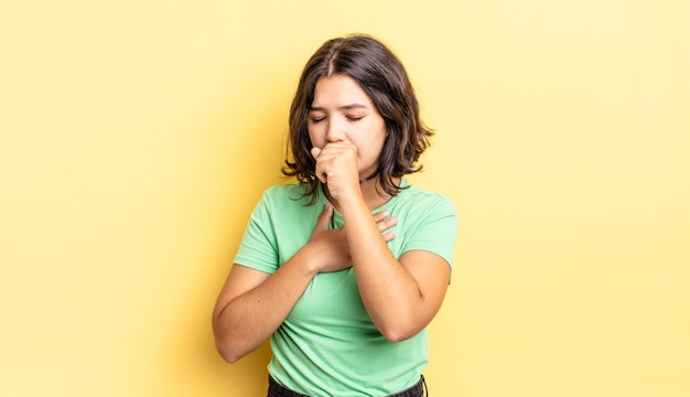 Jeune jolie fille se sentant malade avec un mal de gorge et des symptômes de grippe, toussant avec la bouche couverte
