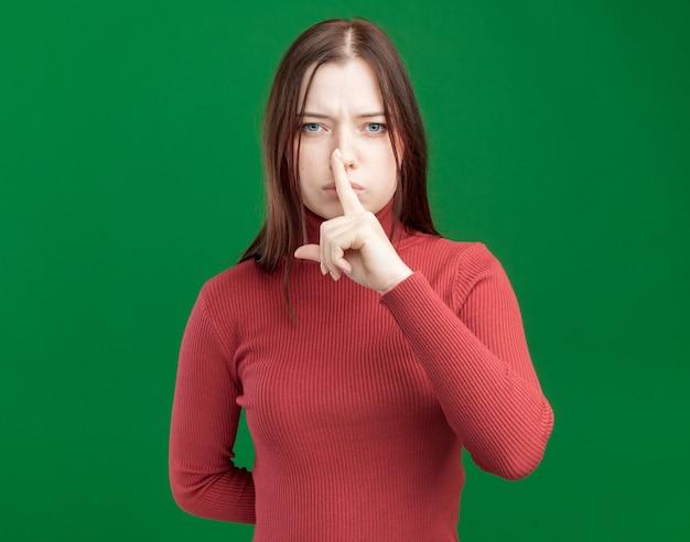 Jeune jolie fille sérieuse faisant un geste de silence en gardant la main derrière le dos isolée sur un mur vert avec espace pour copie