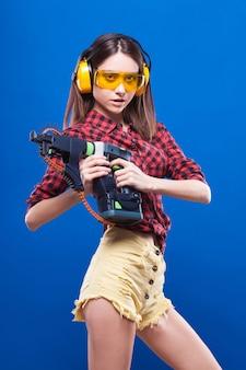 Jeune jolie fille sexy en chemise à carreaux rouge, fabrique des lunettes et cache-oreilles pour tenir le perforateur