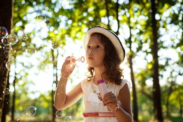 Jeune jolie fille soufflant des bulles, marchant dans le parc au coucher du soleil.