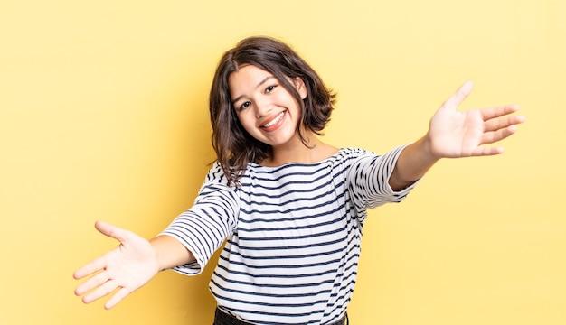 Jeune jolie fille souriante donnant un câlin de bienvenue chaleureux, amical et affectueux, se sentant heureuse et adorable