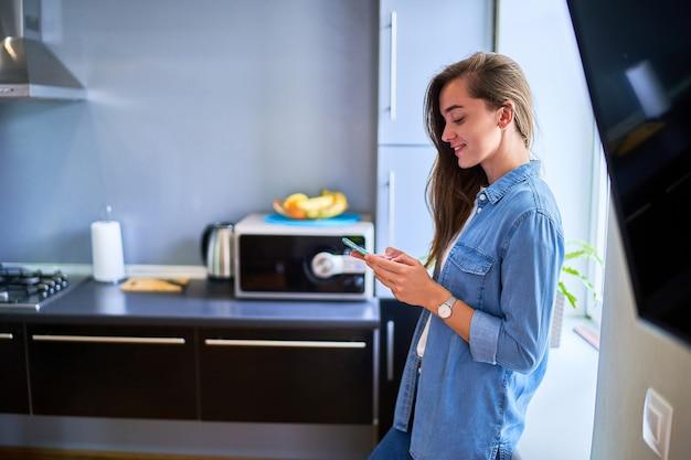 Jeune jolie fille souriante heureuse mignonne du millénaire debout à la fenêtre et utilisant le téléphone pour discuter en ligne, surfer sur le web, surfer et sur les réseaux sociaux à la maison