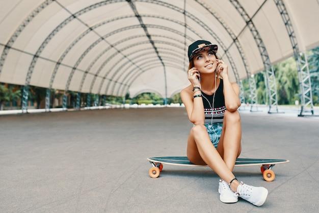 Jeune jolie fille souriante avec un longboard