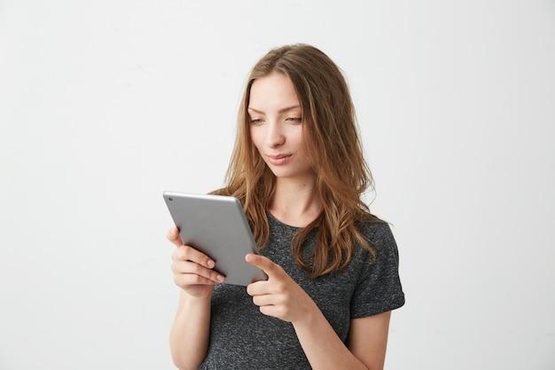 Jeune jolie fille souriante regardant tablette surfer sur le web, naviguer sur internet.