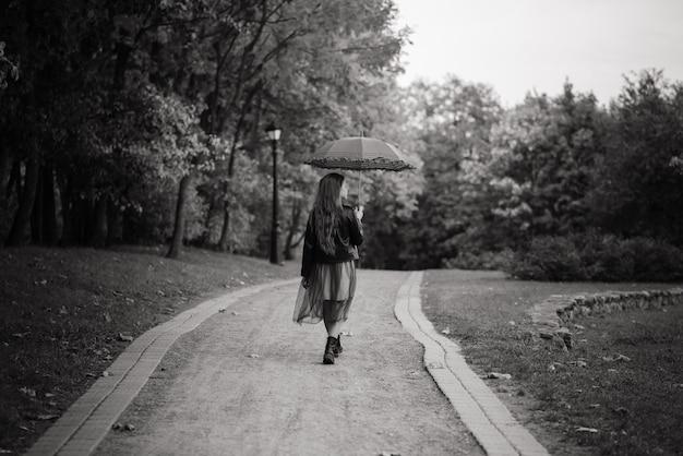 Jeune jolie fille souriante sous parapluie dans une forêt d'automne