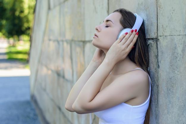 Jeune jolie fille en t-shirt blanc écoutant de la musique tout en s'appuyant contre le mur