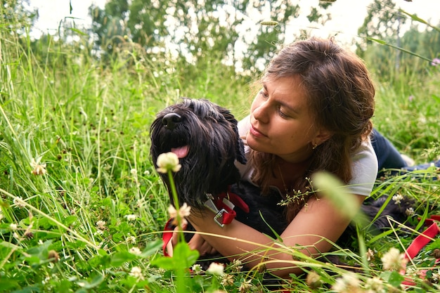 Une jeune jolie fille en t-shirt blanc se trouve sur l'herbe dans la nature avec un chien mittelschnauzer noir