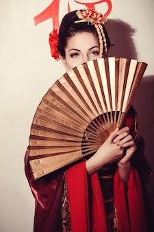 Jeune jolie geisha en kimono avec sakura et décoration