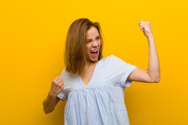 Jeune jolie jeune femme levant son poing après une victoire