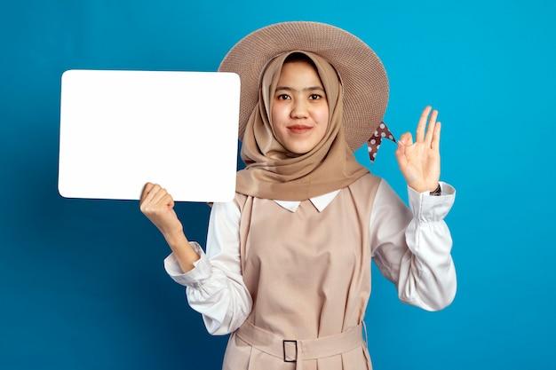 Jeune jolie jeune femme musulmane asiatique portant un chapeau ayant un tableau blanc